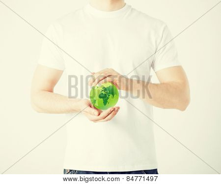 environment and technology concept - man hands holding green sphere globe
