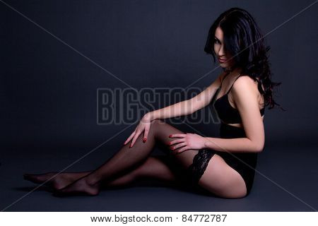 Beautiful Sexy Seductive Woman In Black Lingerie Sitting On The Floor Over Grey