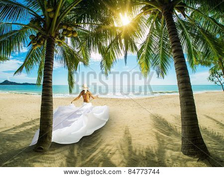 Beautiful classy woman on the beach with white sarong. Thailand.