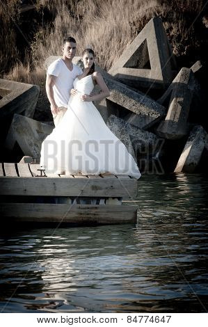 Young in love bridal couple standing at water's edge