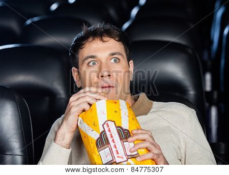 Frightened man eating popcorn while watching movie in cinema theater