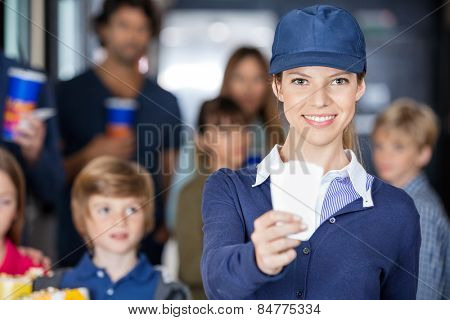 Portrait of happy female worker holding tickets while families waiting in background at cinema