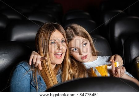 Cute girl showing something to shocked mother while watching movie in cinema theater