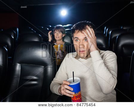 Terrified people watching film in movie theater