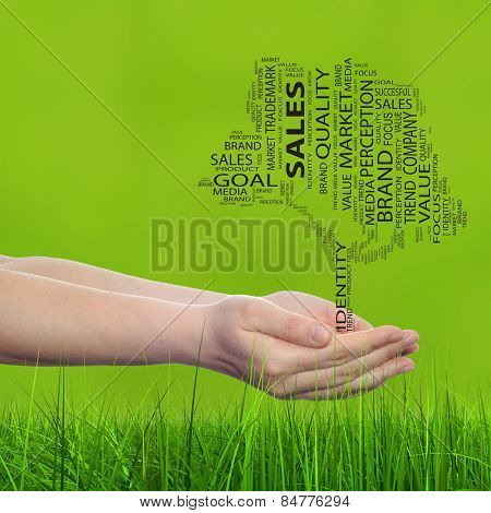 Concept conceptual tree word cloud tagcloud in man or woman hand green blur grass background metaphor to business, trend, media, focus, market, value, product, advertising, success sale or corporate