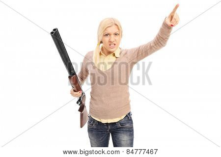 Angry woman holding a rifle and pointing with finger isolated on white background