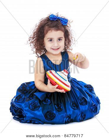 cute little girl sitting on the floor and holding a dreidel