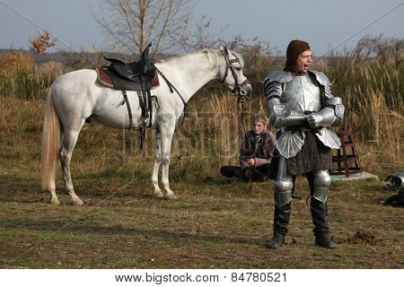 MILOVICE, CZECH REPUBLIC - OCTOBER 23, 2013: Actor dressed as a medieval knight and his horse during the filming of the new movie The Knights near Milovice, Czech Republic.
