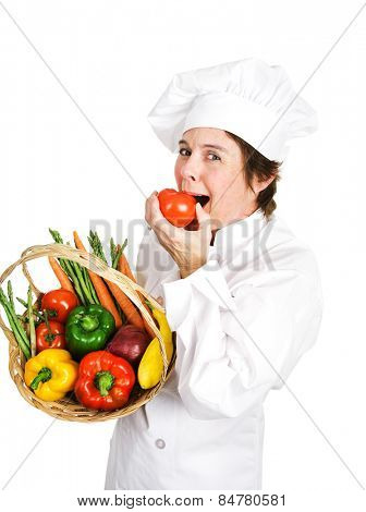 Chef holding a basket of fresh vegetables takes a bit out of a ripe tomato.  Isolated on white.