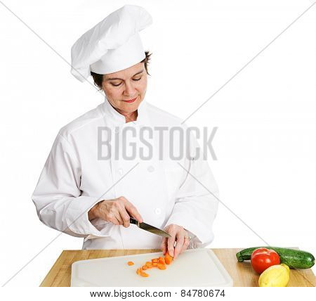 Pretty female chef chopping vegetables on a cutting board.  Isolated on white.