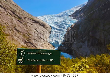 Sign - Melting Briksdal glacier - Norway - nature and travel background