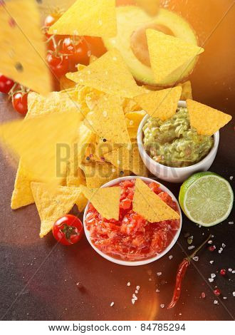 Guacamole with nachos in freeze motion, close-up.