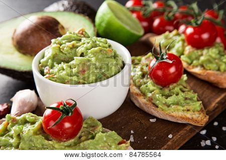 Guacamole with bread and avocado on stone background