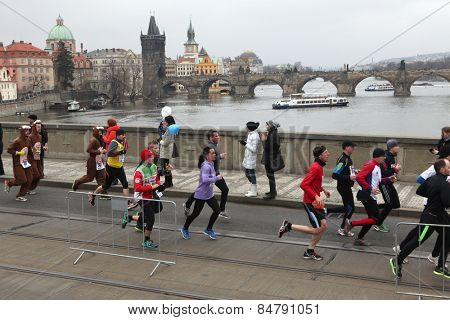 PRAGUE, CZECH REPUBLIC - APRIL 6, 2013: Athletes run over the Manes Bridge on the Vltava River during the Prague international marathon in Prague, Czech Republic.