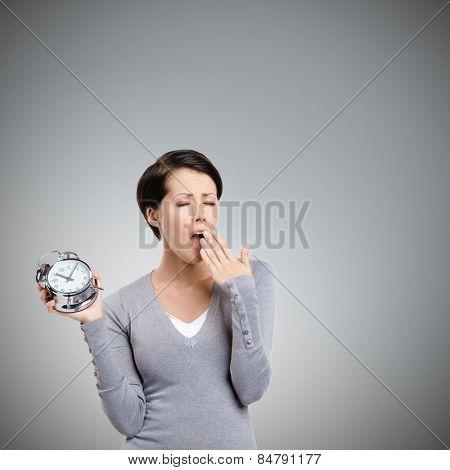 Sleeping pretty woman holds an alarm clock, isolated on grey