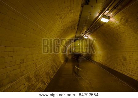 Cyclist walking through tiled Thames tunnel on commute in Greenwich, London