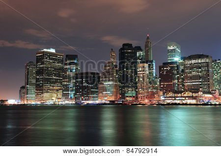 New York City Manhattan downtown skyline with skyscraper and water reflection over East River at night