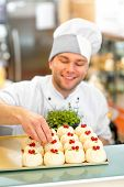 stock photo of confectioners  - Handsome confectioner in uniform decorating cake with currant - JPG