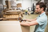 picture of warehouse  - Warehouse worker preparing a shipment in a large warehouse - JPG