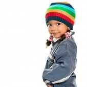 foto of beanie hat  - Funny mixed race small girl wearing winter clothes and a colorful beanie hat isolated on white - JPG