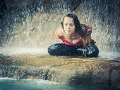 stock photo of padmasana  - Woman practicing yoga near waterfall - JPG