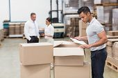 picture of warehouse  - Warehouse manager checking his inventory in a large warehouse - JPG
