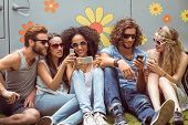 pic of friendship day  - Hipster friends using their phones on a summers day - JPG