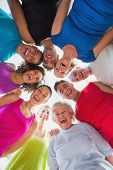 stock photo of huddle  - Low angle portrait of cheerful people forming huddle at gym - JPG