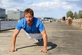 Постер, плакат: Sport fitness man push ups Male athlete exercising push up outside in urban city boardwalk Fit mal