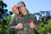 foto of reunited  - Handsome soldier reunited with partner on a sunny day - JPG