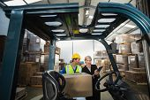 foto of forklift driver  - Warehouse manager talking with forklift driver in a large warehouse - JPG