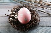stock photo of pussy-willows  - Bird colorful egg in nest and pussy willow branches on wooden background - JPG