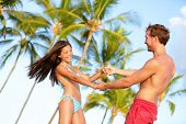 stock photo of lovers  - Beach couple fun on vacation dancing playful - JPG