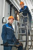 stock photo of fuse-box  - two electrician builder engineers workers installing industrial cable into fuse box - JPG