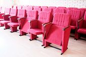 foto of recliner  - Large red recliners stand rows in an empty hall  - JPG