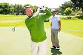 stock photo of take off clothes  - Golfing friends teeing off at the golf course - JPG