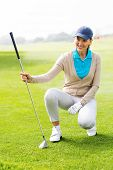 foto of knee-cap  - Female golfer kneeing on the putting green on a sunny day at the golf course - JPG
