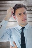foto of scratching head  - Thinking businessman scratching head against wooden planks - JPG