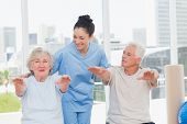stock photo of senior class  - Happy trainer assisting senior couple to exercise in gym - JPG