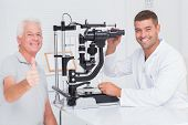 image of slit  - Portrait of happy senior man showing thumbs up while sitting with optician in clinic - JPG
