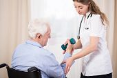 foto of nurse practitioner  - Practitioner showing disabled patient exercise with dumbbell - JPG