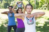 stock photo of kettles  - Fitness group working out in park with kettle bells on a sunny day - JPG