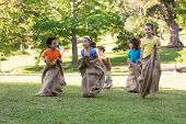 stock photo of friendship day  - Children having a sack race in park on a sunny day - JPG