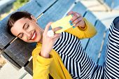 pic of yellow  - Woman in yellow having video call or taking selfie photo with yellow phone on wooden sunbed - JPG