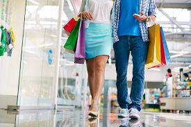 foto of jeans skirt  - Legs of young couple of shoppers walking down mall - JPG