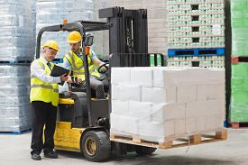 picture of forklift  - Forklift driver talking with his manager in a large warehouse - JPG