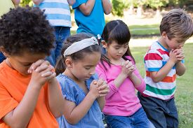 stock photo of prayer  - Children saying their prayers in park on a sunny day - JPG