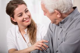 stock photo of nursing  - Picture of smiling nurse assisting senior man - JPG