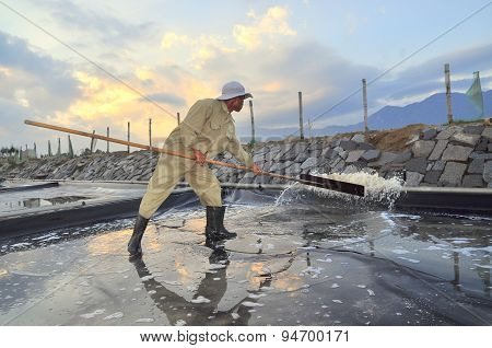 Ninh Hoa, Vietnam - March 2, 2012: A Worker Is Slapping Water Out Of The Salt Extracting Field In Th