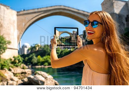 Woman photographing old bridge in Mostar city
